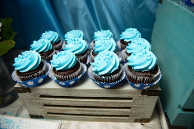 Chocolate cupcakes with blue glaze and pearls stand on wooden box