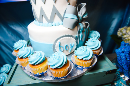 Pretty cupcakes with blue glaze stad around cake with lettering 'Boy'