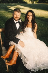 Happy groom holds bride's legs in boots on his knees