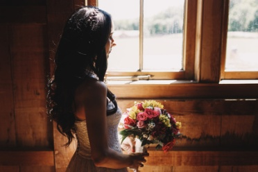Sun shines over a brunette woman standing with wedding bouquet before a window