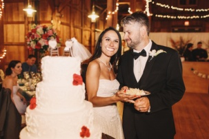 Bride smiles with wedding cake in her mouth while standing behind a groom