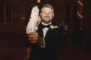 Happy bearded groom holds white garter in his hand
