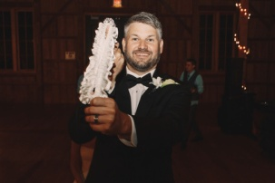 Happy bearded groom holds white garter in his hand
