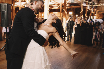 Groom bends brunette bride over while dancing in the wooden hall