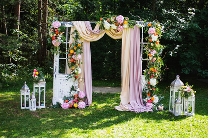 Beautiful wedding ceremony outdoors. Wedding arch made of cloth and white and pink flowers on a green natural background. Old doors, rustic style.